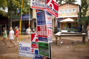 Post covered in political yard signs in middle of town