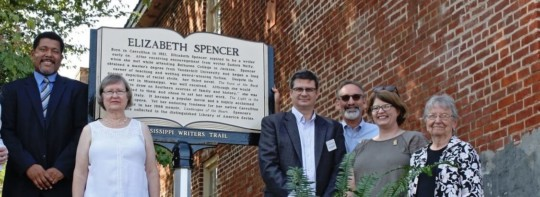 Group posed before Elizabeth Spencer plaque
